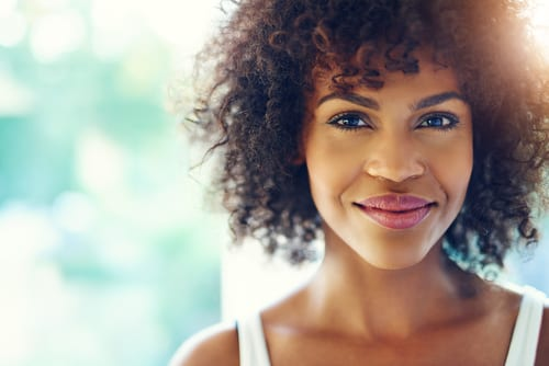Portrait of smiling young black woman with sunlight flare and copy space-img-blog